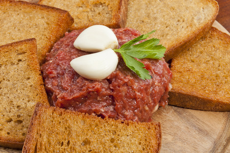 trencher: Steak tartar ready to eat on the wooden trencher
