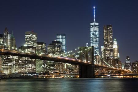De skyline in de nacht New York City w Brooklyn Bridge en Freedom Tower