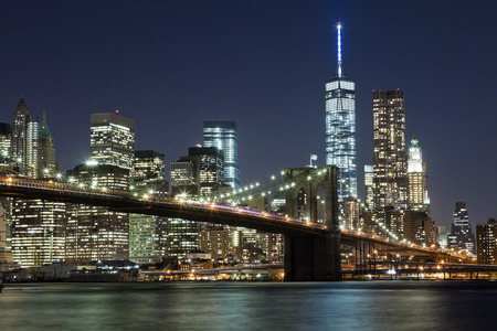 cities: The New York City skyline at night w Brooklyn Bridge and Freedom tower Stock Photo