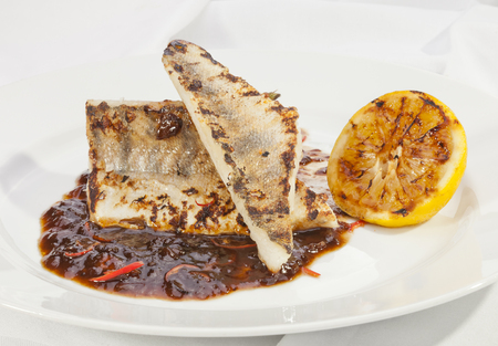 pikeperch: Grilled Pike perch with lemon and tomato sauce Stock Photo