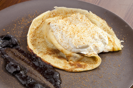 cram: Crepe pancake with whipped cram and gingerbread powder Stock Photo