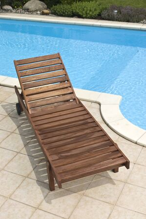 A wooden garden deckchair standing by the pool