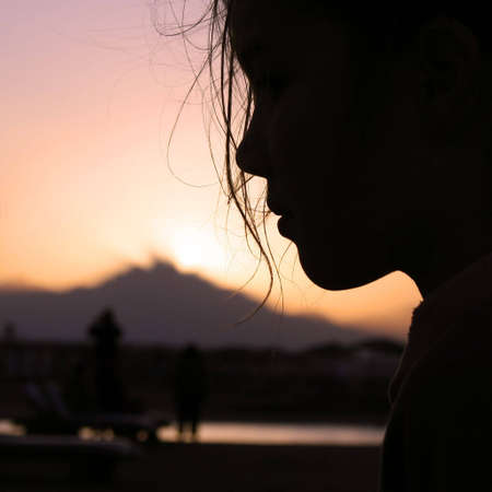 end of a long day: Twilight in egyptian beach: Sunset in Egypt, profile of young girl with mountains in background, pink twilight