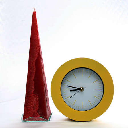 lifespan: Purple, conical, unused candle with white wick and yellow, round, analog clock with hands side by side
