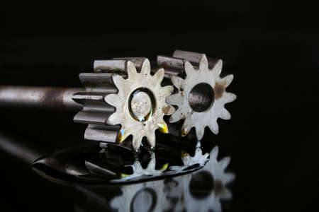 profiled: Cogs of oil pump with puddle od motor oli. Element with rust, yellow oil, black bacground.