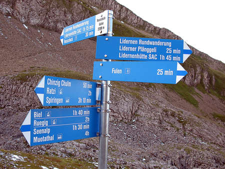 view of five blue, steel directional signs on a pole. Signs showing distances to hiking goals.  Stock Photo - 9145539