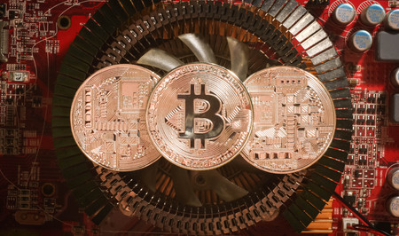 three silver coins bitcoin are on the heatsink of the video card in the red light