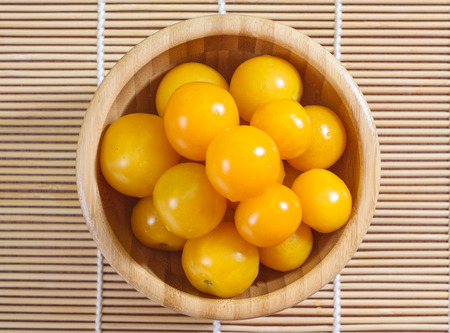yellow cherry tomatoes in a wooden bowl, top view