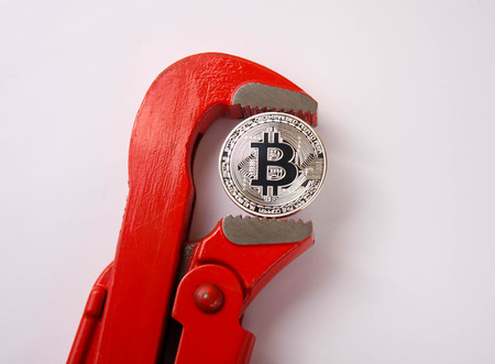red pipe spanner clamps a silver coin bitcoin, a white bacground