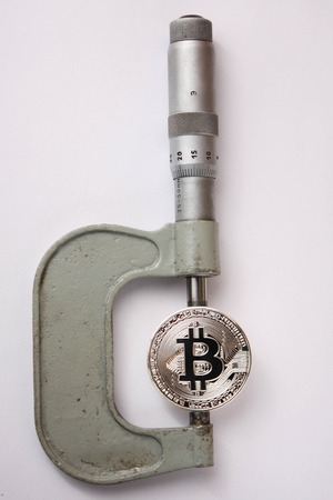 the bitcoin is measured with a micrometer on a white background Banque d'images
