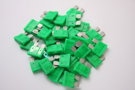 several green car fuses on a white background