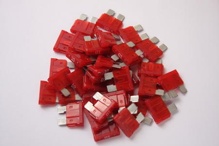 several red car fuses on a white background