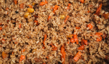 Background Uzbek pilaf. Texture of a fresh dish with rice, onions, carrot and meat
