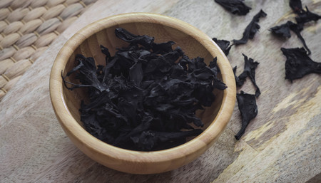 Delicious dried black chanterelles in a bowl on a wooden table