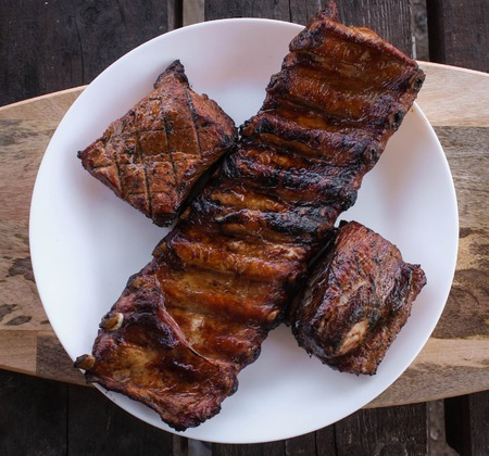 Grilled and smoked pork ribs on a white plate on a wooden board