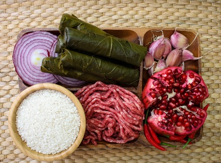 Raw ingredients for cooking dolma. Grape leaves, beef and pomegranate. top view