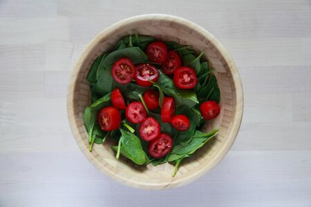Spinach and tomato vegetable salad in a wooden bowl. Top view
