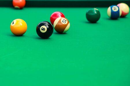 Veelkleurige biljartballen op groene doek.