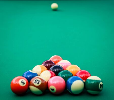 A triangle of colored billiard balls on a green cloth. Daylight illumination