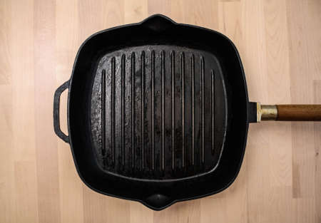 Close-up of an empty black grill pan on a wooden background, top view. Copyspace