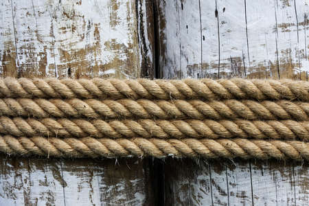 Four layers of rope tied around a wooden log, in the shade on a sunny day
