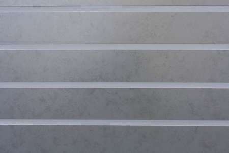 Gray ceramic tile with convex horizontal lines for wall and floor decoration. Concrete stone surface background.