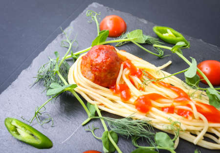 Meat meatballs and spaghetti with herbs were served as a comet with a tail on a basalt plate. 版權商用圖片