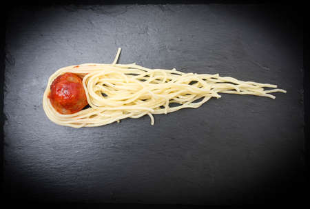 Meat meatball and spaghetti served as a comet with a tail on a basalt plate