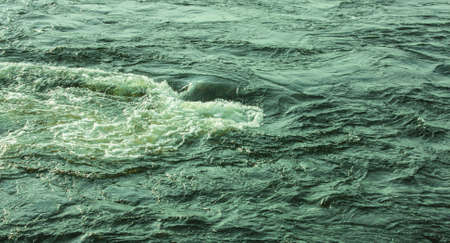 stormy rapids on the water. Photo with a green filter. Solar illumination