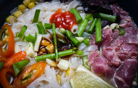 Vietnamese Pho Bo soup with rice noodles, beef and vegetables