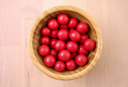 Delicious candies, nuts in red glaze lie in a bowl made of bamboo.