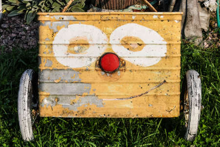 An old garden cart with a funny face painted on it