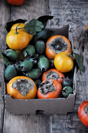 On the table in a box a fresh persimmon, feijoa and citrus mandarins