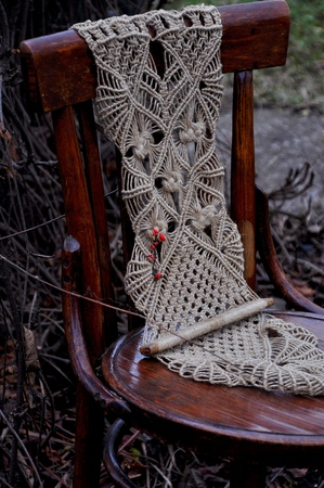 Macrame handmade on a wooden chair in the garden. The background of dyad