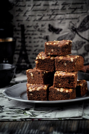 Brownie with pine nuts. Dark background. Rustic style