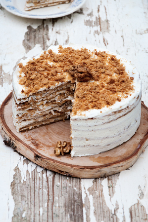 On a wooden background a honey cake with walnuts in a cut. Rustic style