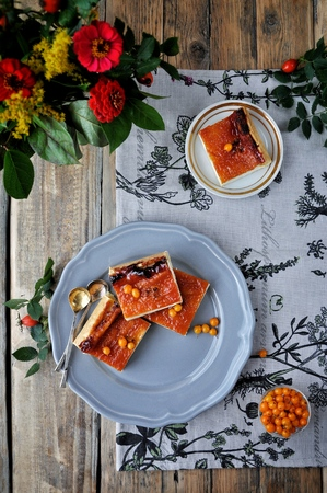 On the wooden plate is a curd cake with a sea-buckthorn. Decorated with flowers and a branch with hips. View from above