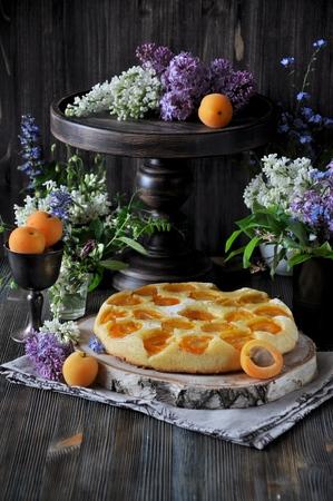 On a wooden stand, a pie with fresh apricots. Against the background a bouquet of lilacs. Wooden table. Rustic style
