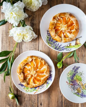 Homemade open apricot pie (shortcrust pastry with apricot filling, peonies in the background). On a wooden kitchen table