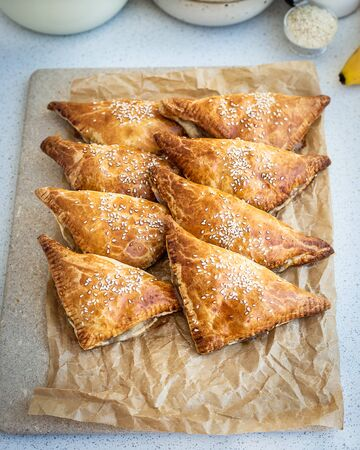 Homemade triangular pies made from ready-made puff pastry with apples