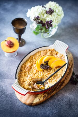 Homemade peach scramble with sand crumbs in a metal baking dish