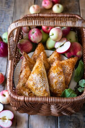 Homemade triangular pies with apples from ready-made puff pastry, in a wooden wicker basket, with fresh apples