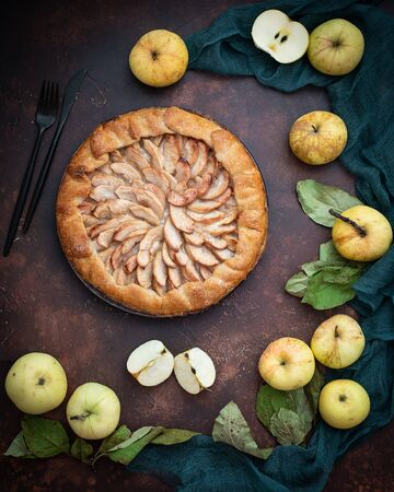 Open apple pie, galleta. Around - fresh apples and green leaves