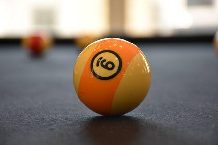 Billiard balls in a Black billiard pool table, focused on 9 ball Archivio Fotografico