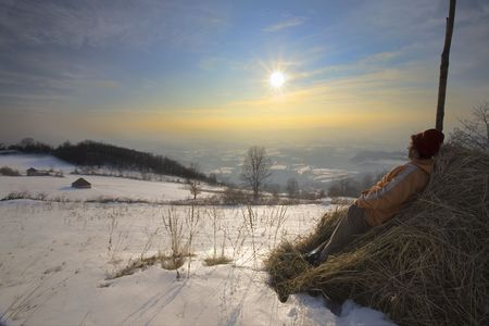 Man enjoying in nature watching his village in the far and sunset, winter season. photo