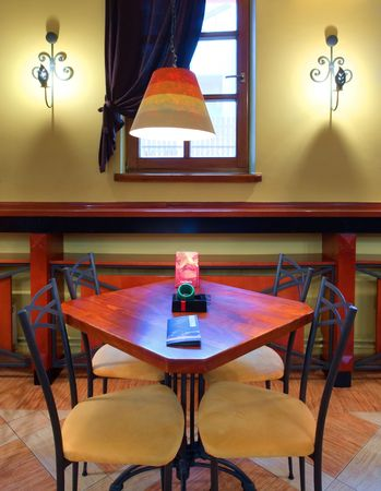 Table and chairs in a cafe-restaurant. Retro design in yellow, red and brown colors. photo