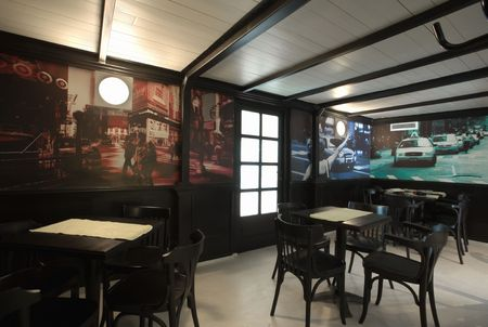 Interior of cafe bar. Designed with street wallpapers and vintage chairs and tables. photo