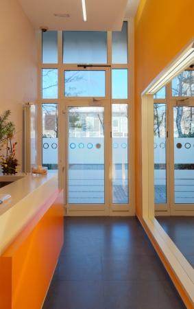 Office entrance, modern and simple in orange and white. Interior of a hall. photo