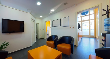 Waiting room. Interior of a dental clinic in orange and white and simple furniture.