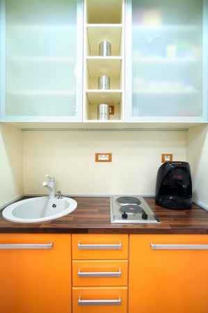 Interior of a small kitchen, orange and white combination of colors with simple furniture.  photo